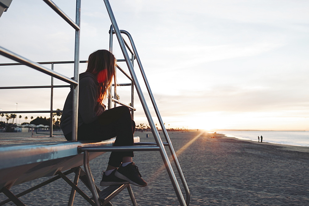 A girl sits on a lifeguard station at dawn looking out to the ocean, Long Beach, California, United States of America