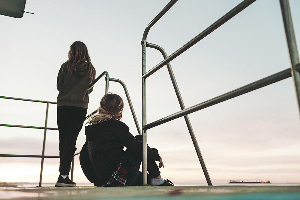 Two girls sit on a lifeguard station at dawn looking out to the ocean, Long Beach, California, United States of America