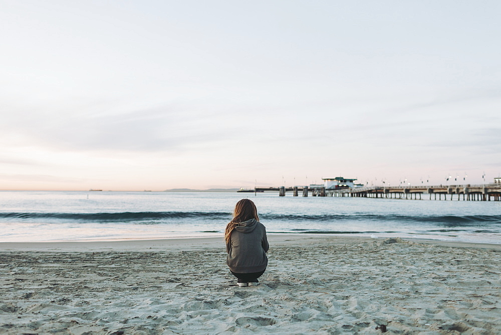 A girl crouches on the beach looking out over the ocean to the horizon at sunset, Long Beach, California, United States of America
