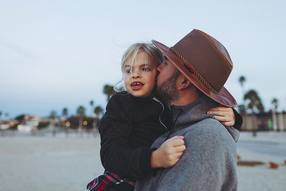 A father and daughter having a tender moment, the father holding his daughter in an embrace on a beach at dusk, Long Beach, California, United States of America