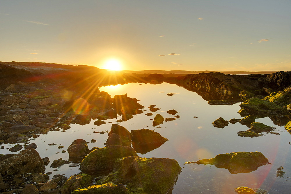 A golden-coloured sunset and sunburst hilights the rocks around an ocean-side pool of water, Chubut, Argentina