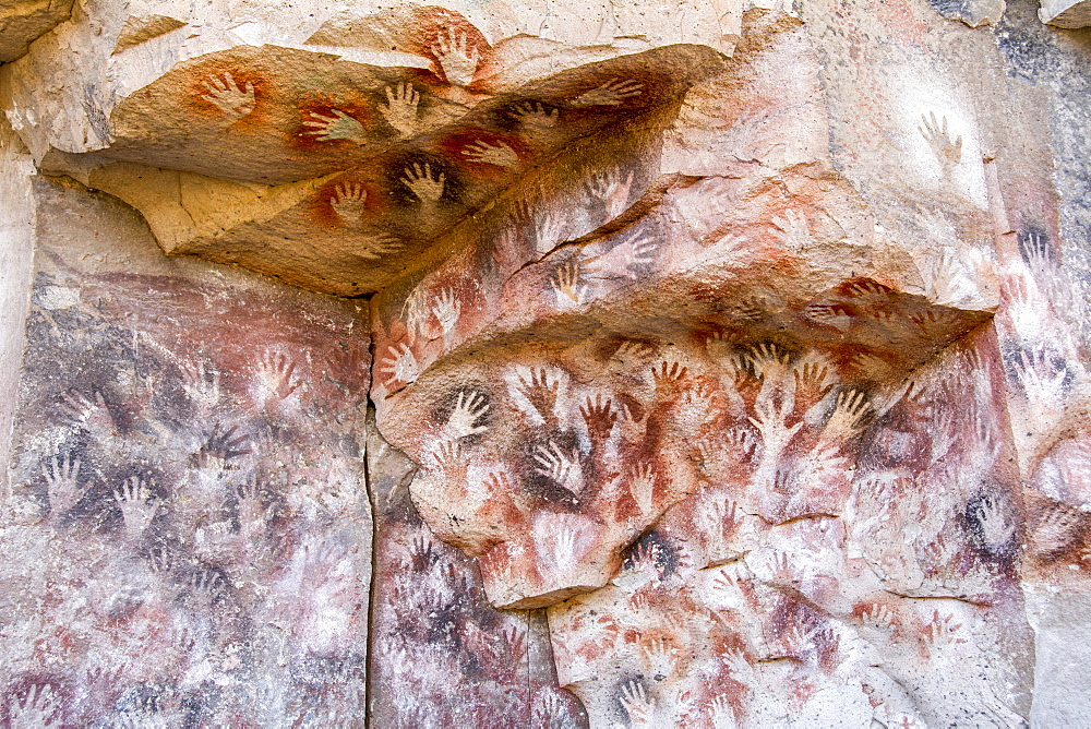 Colourful handprints on a rock face, ochre-ink art made by the long-vanished Toldense People, Santa Cruz, Argentina