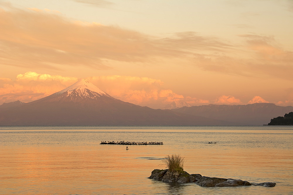 Sunset illuminates a lake and a snow-capped volcano in the distance, Frutillar, Los Lagos, Chile