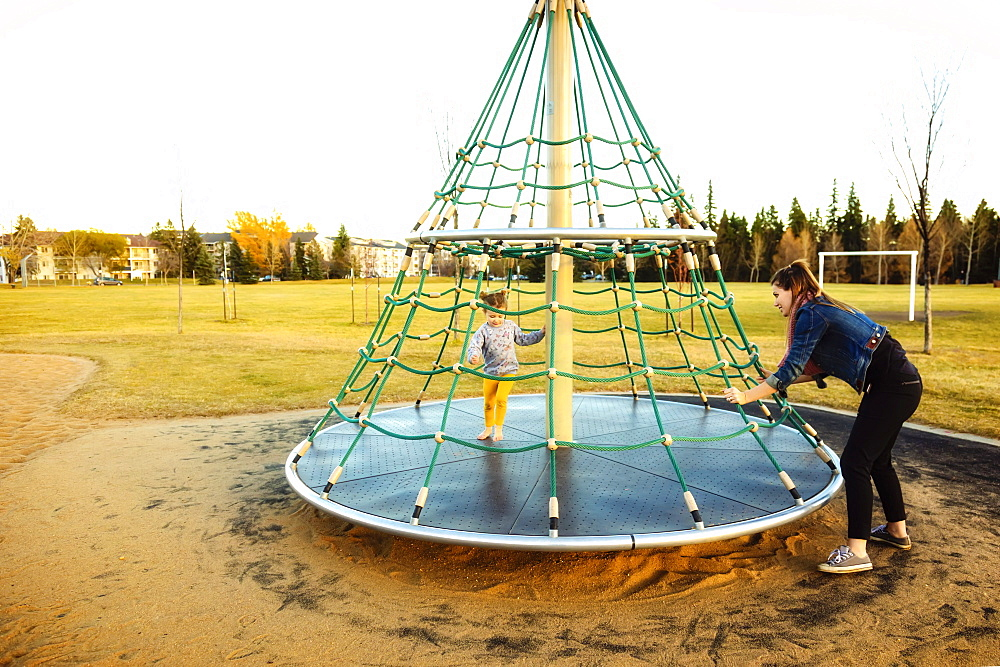 A young mom spinning her daughter while playing on a merry go round with a rope climber in a playground at sunset during a warm autumn evening, Edmonton, Alberta, Canada - 1116-48180