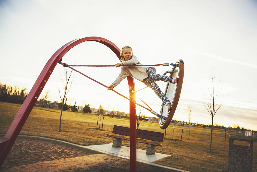 A daring young girl playing on saucer swings in a playground on a warm autumn evening, Edmonton, Alberta, Canada