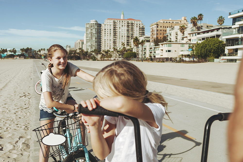 Sisters ride bikes along the beach in Long Beach, Los Angeles, California, United States of America