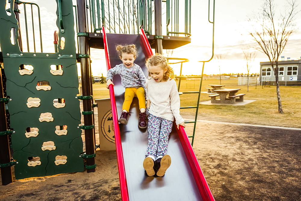 Two young sisters going down a slide in a playground on a warm autumn evening at sunset, Edmonton, Alberta, Canada