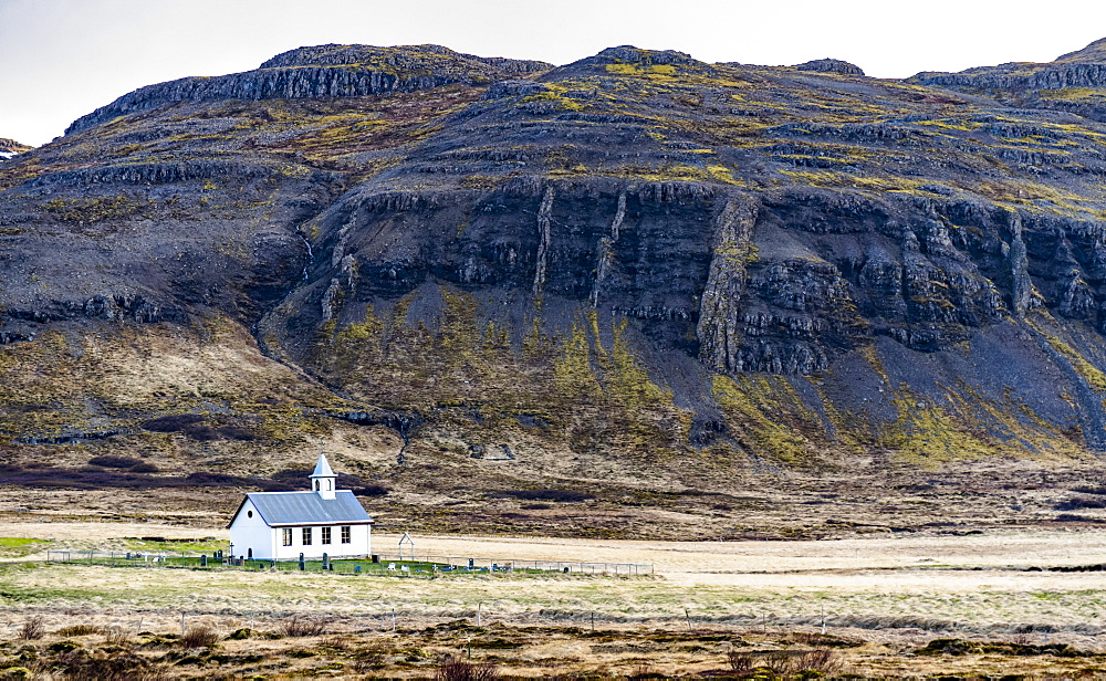 A church and small graveyard are dwarfed by the surrounding nature in Western Iceland, Iceland