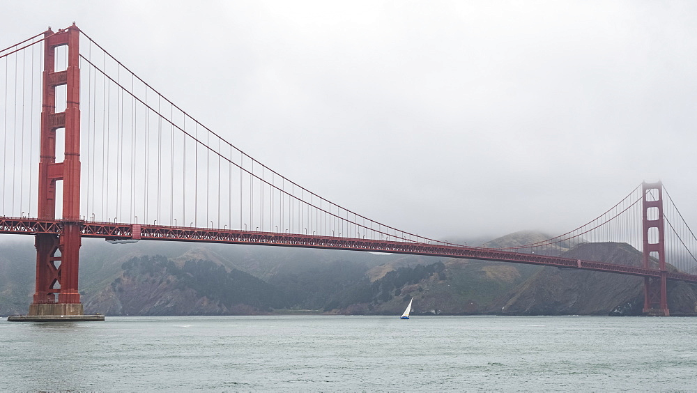 Golden Gate Bridge on a cloudy day with a sailboat on the water below, San Francisco, California, United States of America