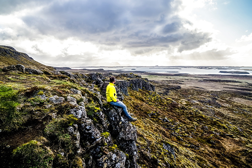 Man looks out over the ocean while sitting on a cliff, Iceland