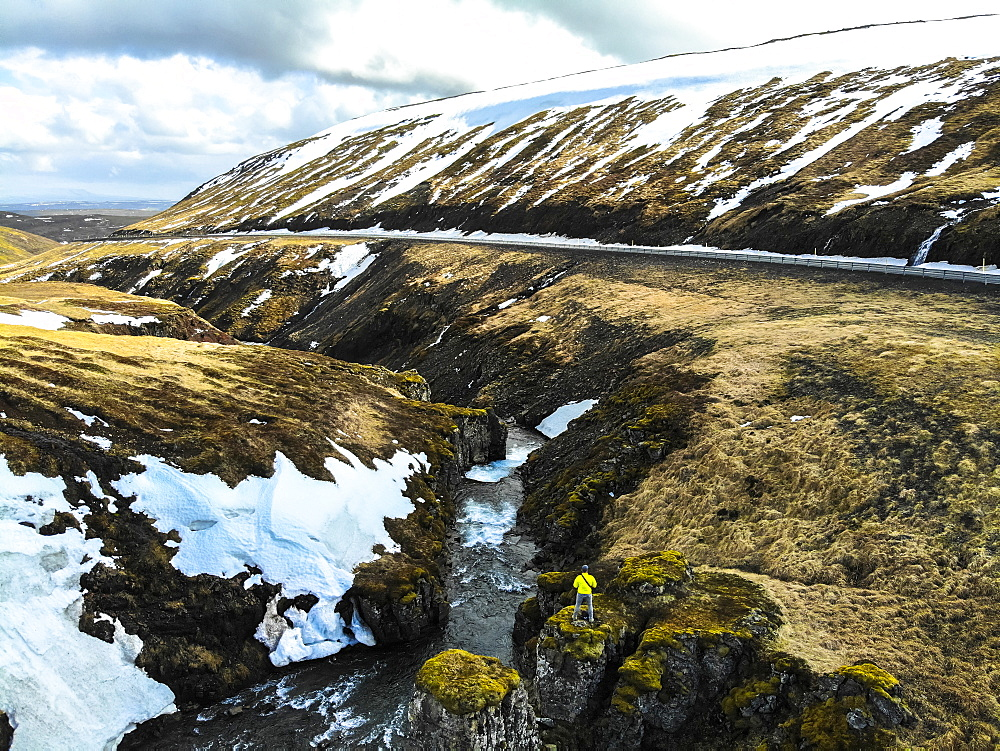 Man observing river next to road in Iceland. Image taken with a drone, Grundarefjorour, Iceland
