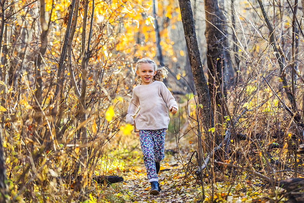 A young girl running through the woods in a city park on a warm fall evening, Edmonton, Alberta, Canada