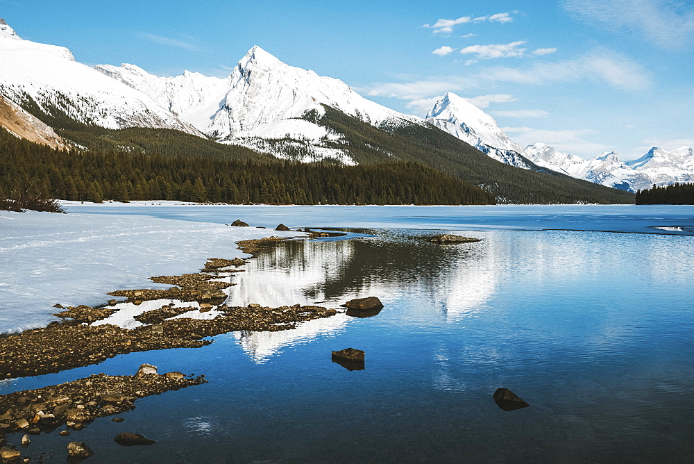 Thawing of a frozen lake and snow-capped rugged mountains peaks, Jasper National Park, Alberta, Canada