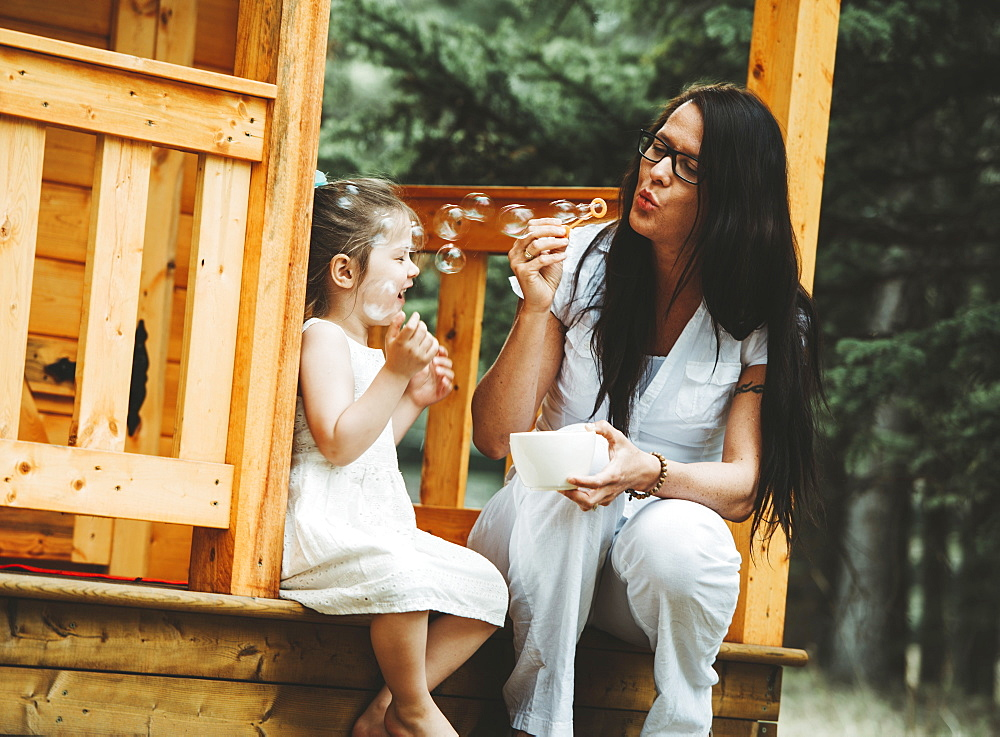 Mother and young daughter blowing bubbles on the steps of a wooden playhouse, Alberta, Canada