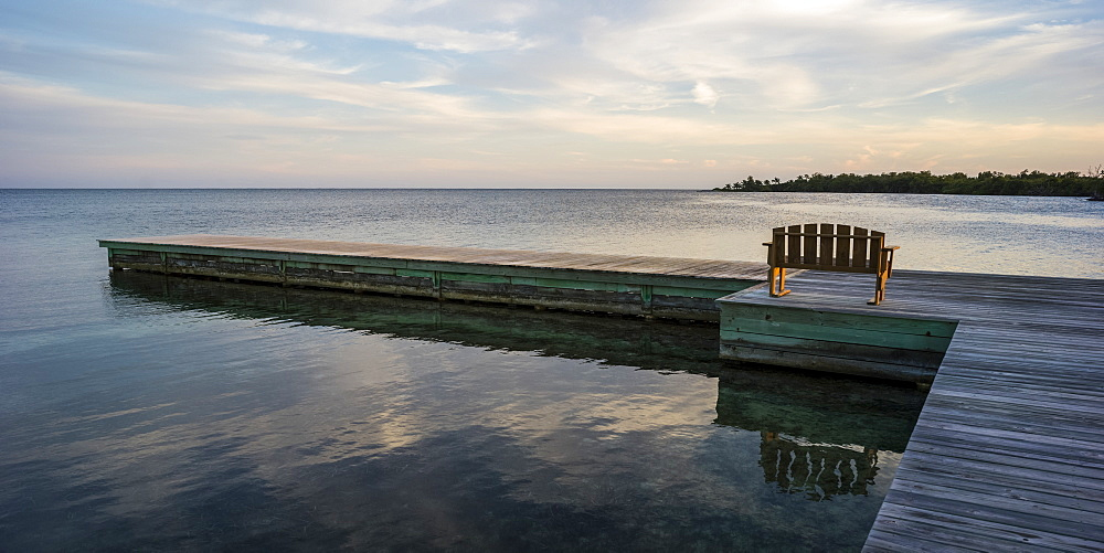A wooden bench on a dock facing the coastline and open ocean at sunrise, Belize