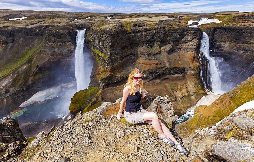 A young female hiker poses for a portrait on the edge of a stunning waterfall valley known as Haifoss, in Southern Iceland, Iceland