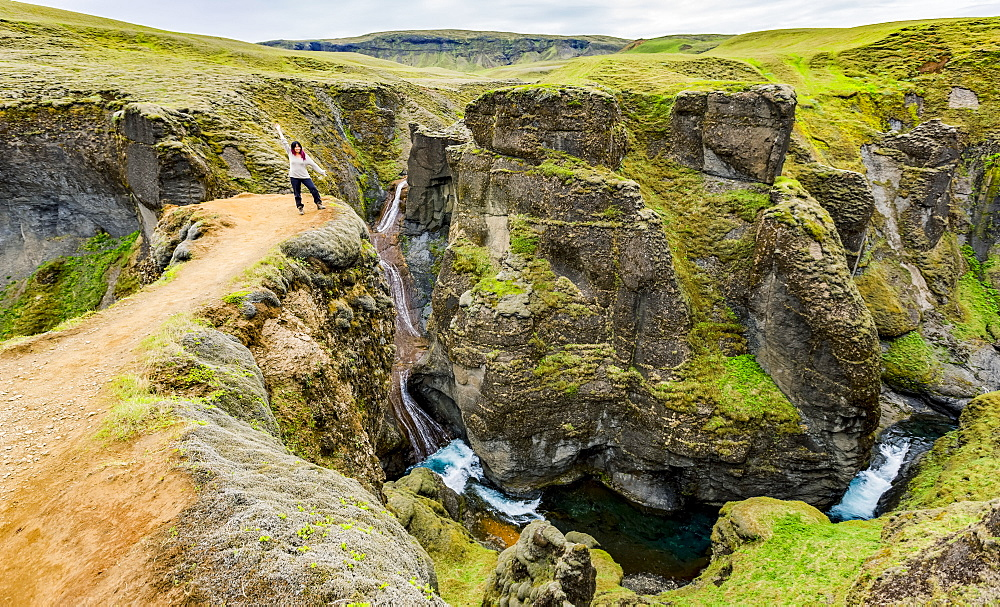 A female tourist stands on a cliff viewpoint in the picturesque valley of Fjadrargljufur in Southern Iceland, Iceland