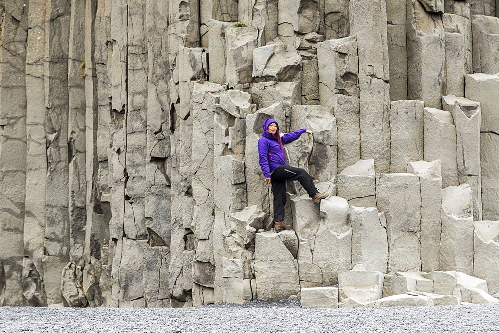 A female tourist poses on the basalt rock columns on the Reynisfjara beach in Southern Iceland, Iceland