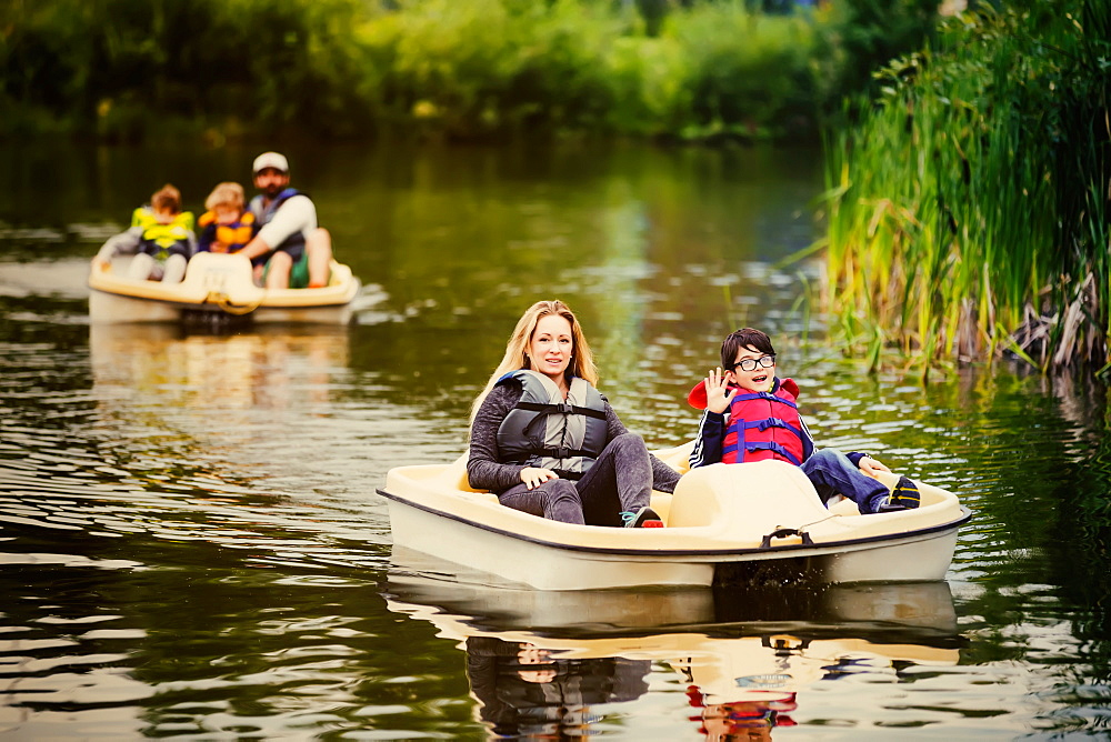 A mother and father take their three sons paddle boating on a lake in a city park, Edmonton, Alberta, Canada