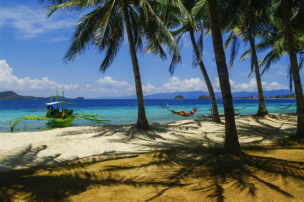 A woman lays on a hammock on a tropical beach with an outrigger canoe moored along the shore, Andaman Islands, India