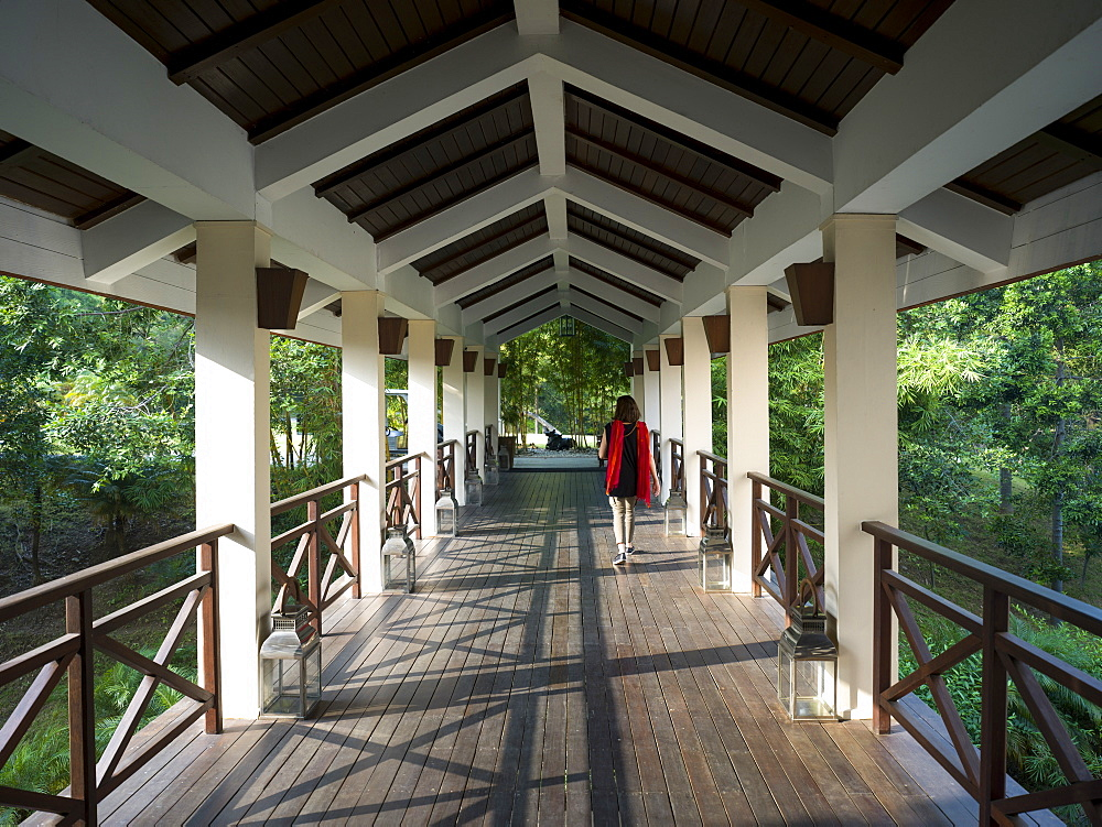 A woman walks down an open-air corridor, Ananda Hotel and Spa, Uttarakhand, India