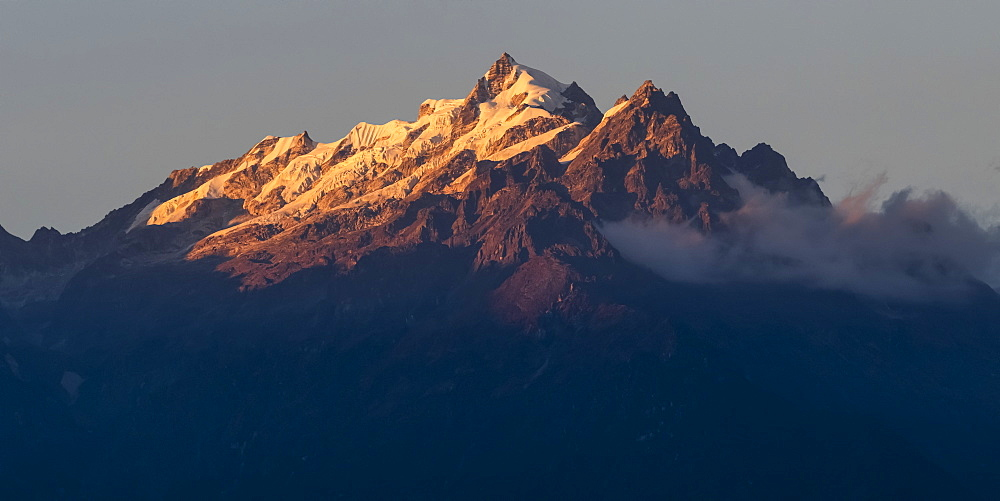 Sunlight illuminating the rugged peaks of the Kangchenjunga Mountain Range, a part of the Great Himalaya Range, Sikkim, India