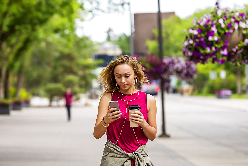 A young woman walking down a street near a university campus texting on her smart phone, Edmonton, Alberta, Canada