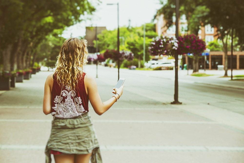 A young woman walks down a path on a university campus reading from her smart phone, Edmonton, Alberta, Canada