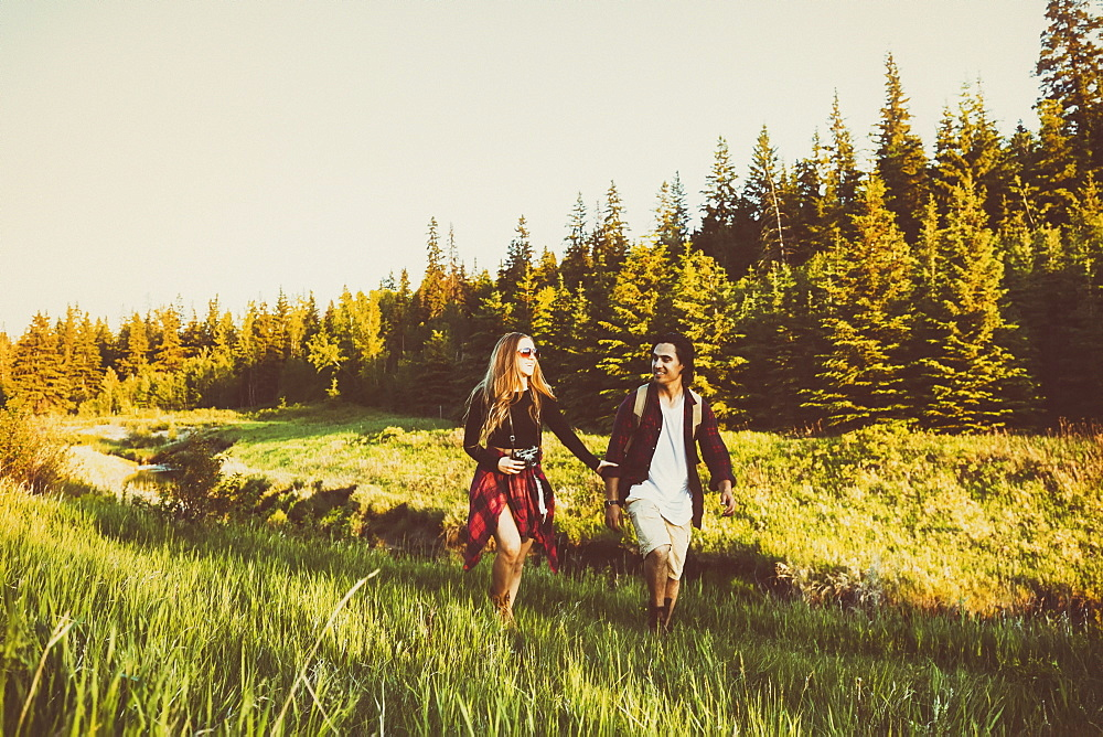 Young couple walking together beside a creek in a city park, Edmonton, Alberta, Canada
