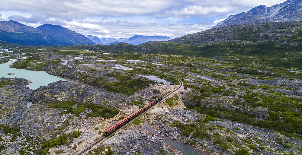 A train runs through the barren landscape on its way to Carcross, Yukon Territory, Canada