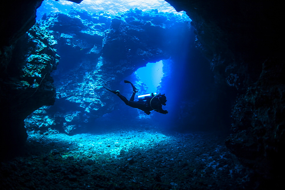 Scuba diver swims through lava arches with sun rays, Cathedrals dive site, Lanai City, Lanai, Hawaii, United States of America