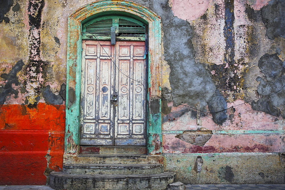 Worn and weathered facade of a building with peeling paint and double doors, Nicaragua