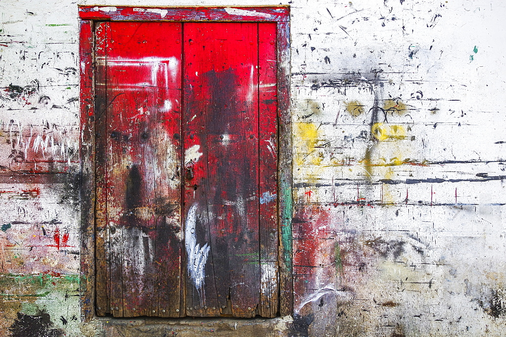 Red wooden doors and wall splattered with multiple paint colours, Nicaragua