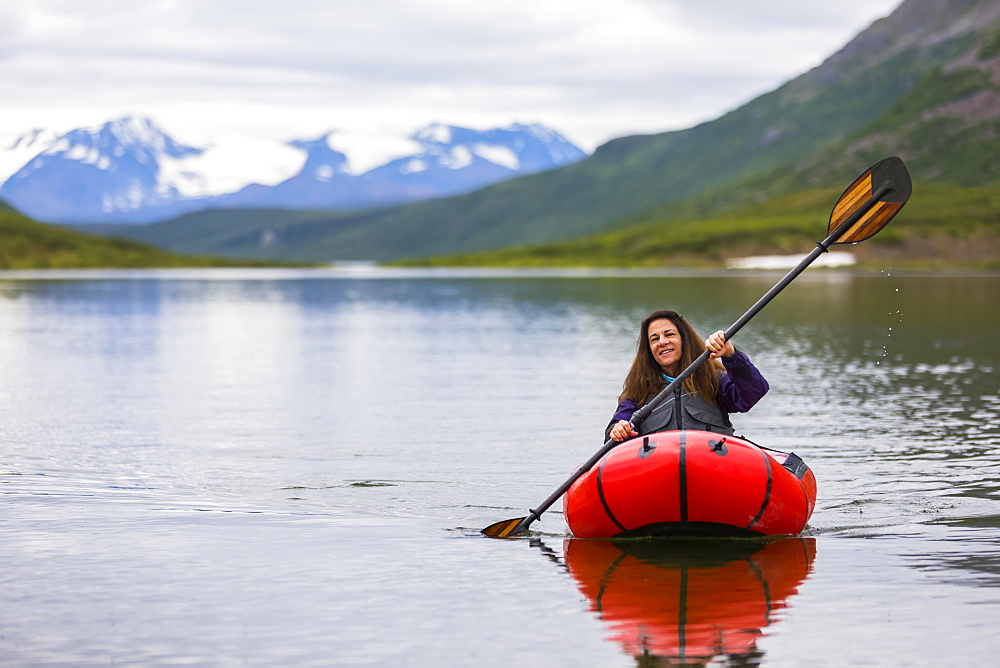 A woman paddles a packraft across Landmark Gap Lake, off the Denali highway, with the Alaska Range in the distance, Alaska, United States of America