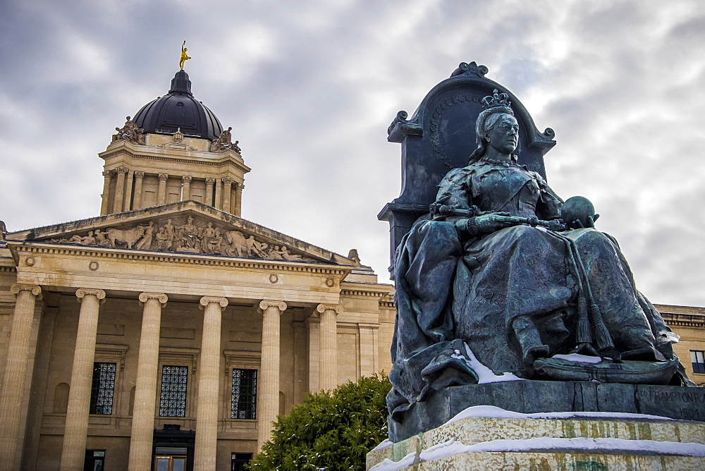 A sculpture of Queen Victoria with the Manitoba Legislative Building in the background with a statue of the Golden Boy on top, Winnipeg, Manitoba, Canada