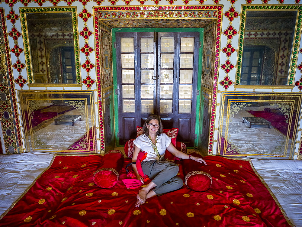 A female tourist sits on the luxurious red rug on the floor of the City Palace, Maharaja Sawai Mansingh II Museum, Mubarak Mahal, Jaipur, Rajasthan, India