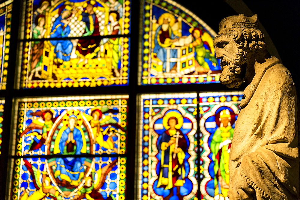 Stone statue with stain glass window in background in a church, Siena, Tuscany, Italy