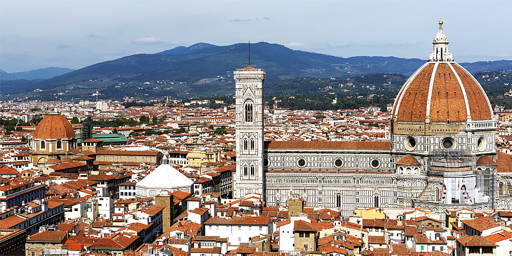Panorama of the city of Florence with Florence Cathedral, it's dome and bell tower, and mountain range in the background, Florence, Tuscany, Italy