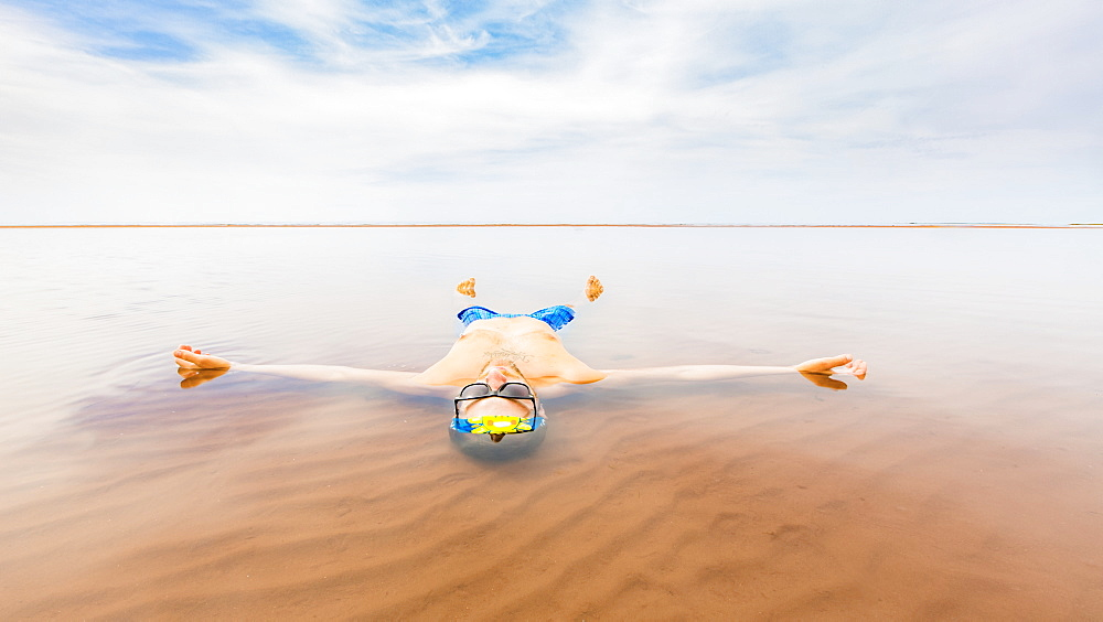 A man wearing a bathing suit floats in the shallow ocean water with his body outstretched and looking up to the sky, Prince Edward Island, Canada