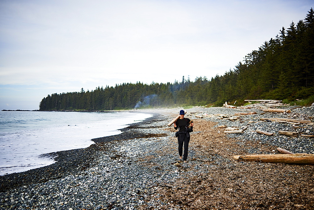 A woman walks along a rocky beach collecting firewood in Cape Scott Provincial Park, Vancouver Island, British Columbia, Canada