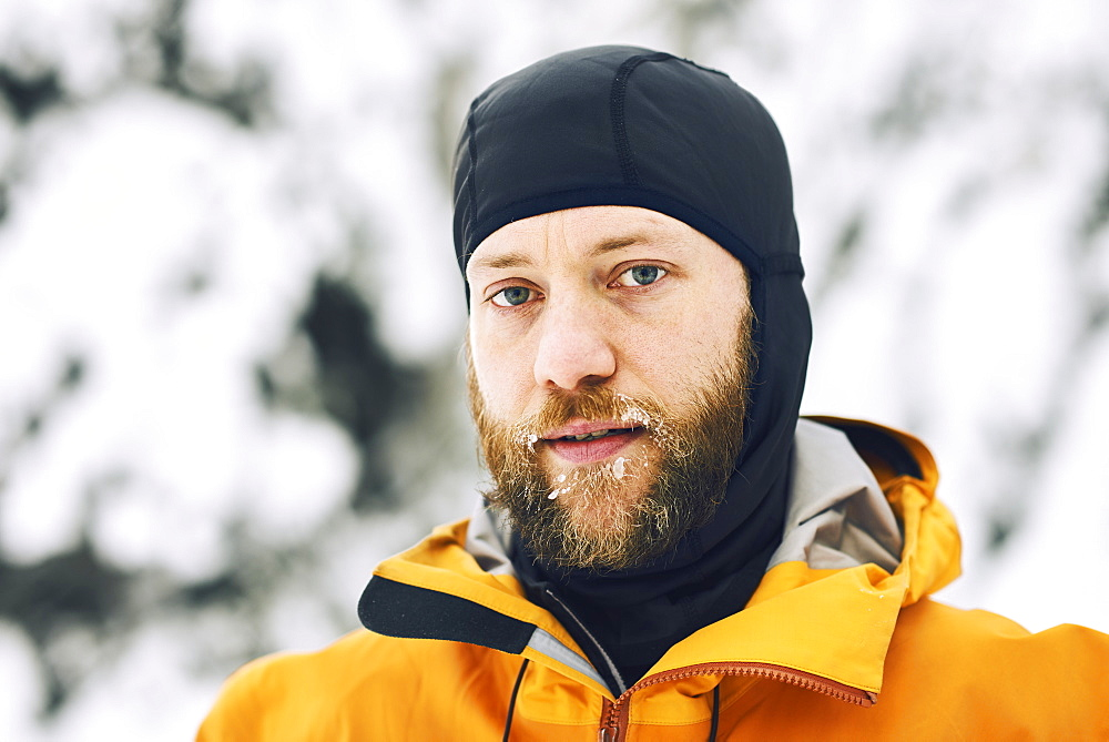 Portrait of a man with a frosty beard wearing a head covering against a snowy background, British Columbia, Canada