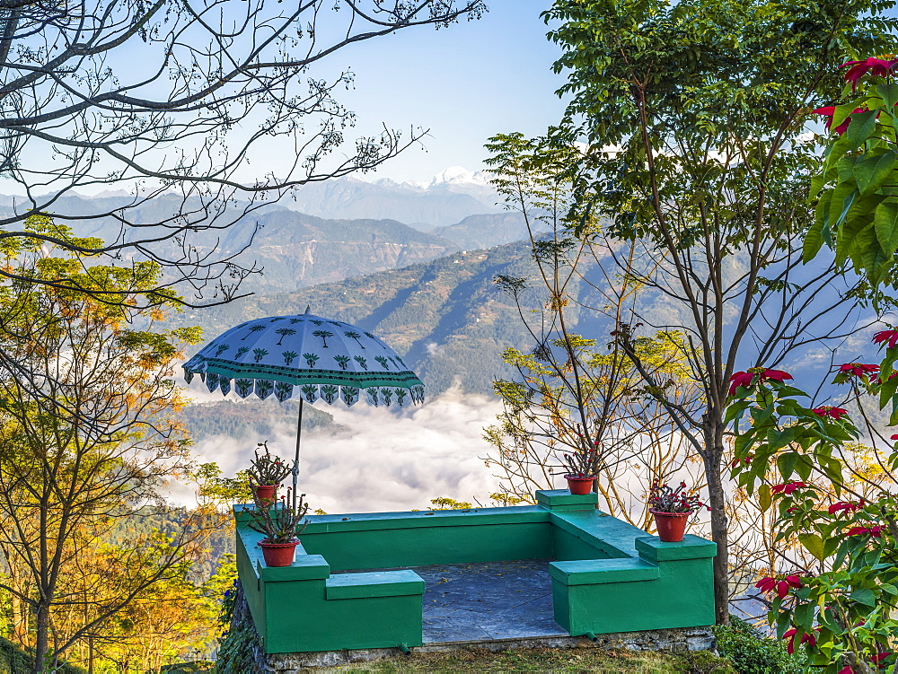 A small green terrace with umbrella decorated with plants and overlooking the mountains and valley, West Bengal, India