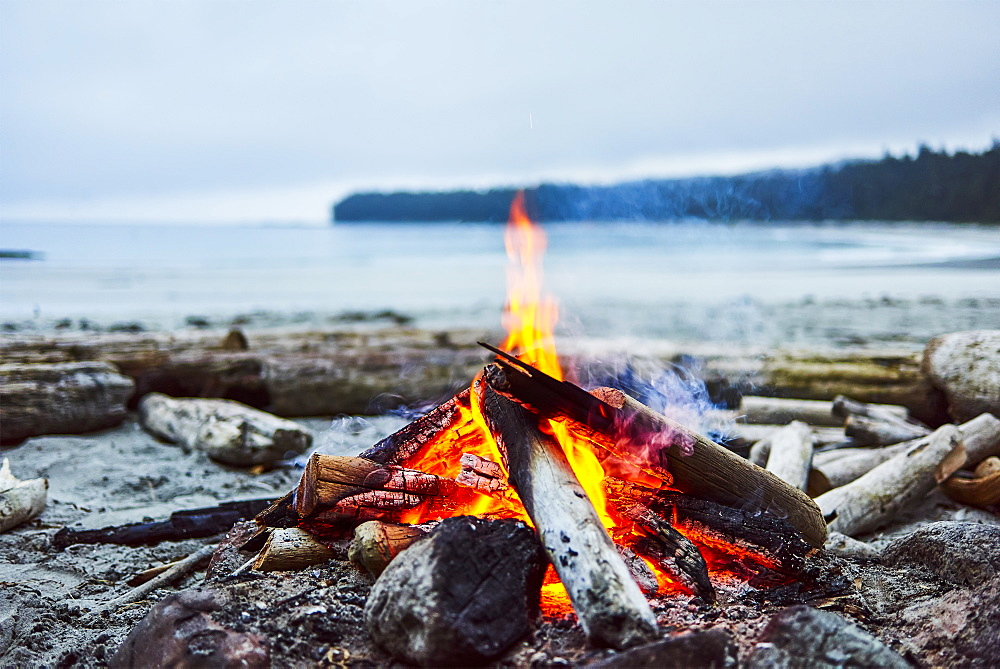 A fire on the beach with the ocean and coastline in the background, Cape Scott Provincial Park, British Columbia, Canada