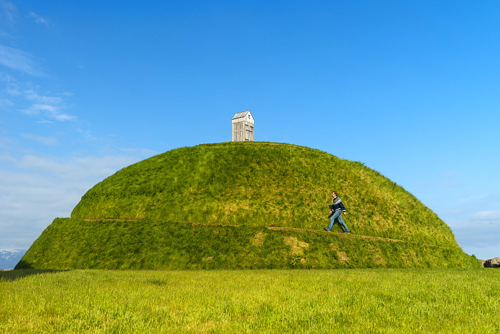 Man walking up Thufa grassy dome with fish drying house on top (art installation by Olof Nordal), Reykjavik, Iceland