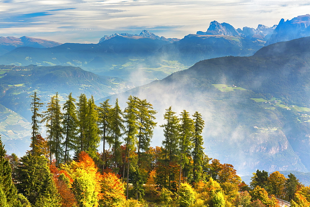 Colourful trees in autumn on a ridge overlooking rolling valley alpine slopes and mountains in the background with mist coming up from the valley, Caldaro, Bolzano, Italy