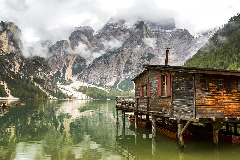 Wooden lake boat house with misty clouded mountain in the background and lake reflection, Sesto, Bolzano, Italy