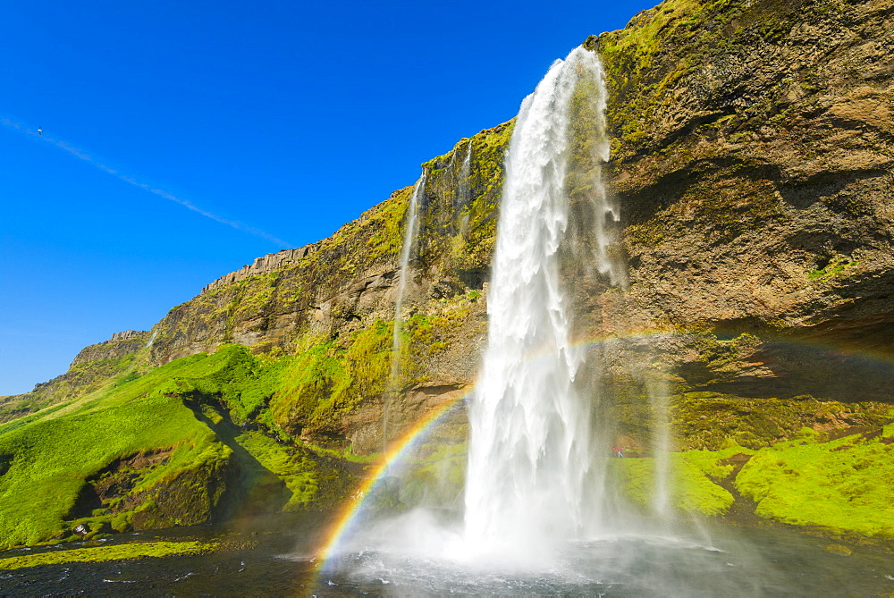 Skogafoss waterfall with blue sky and a rainbow in the mist, Iceland