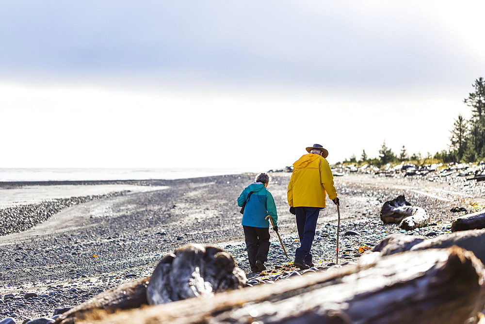 A senior couple hiking with walking sticks on the beach along the coast, Meadow Mist Campground, Graham Island, Tlell, Haida Gwaii, British Columbia, Canada