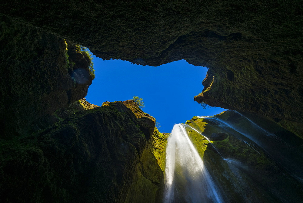 Looking up to a small waterfall in large hole near Seljalandsfoss, Iceland