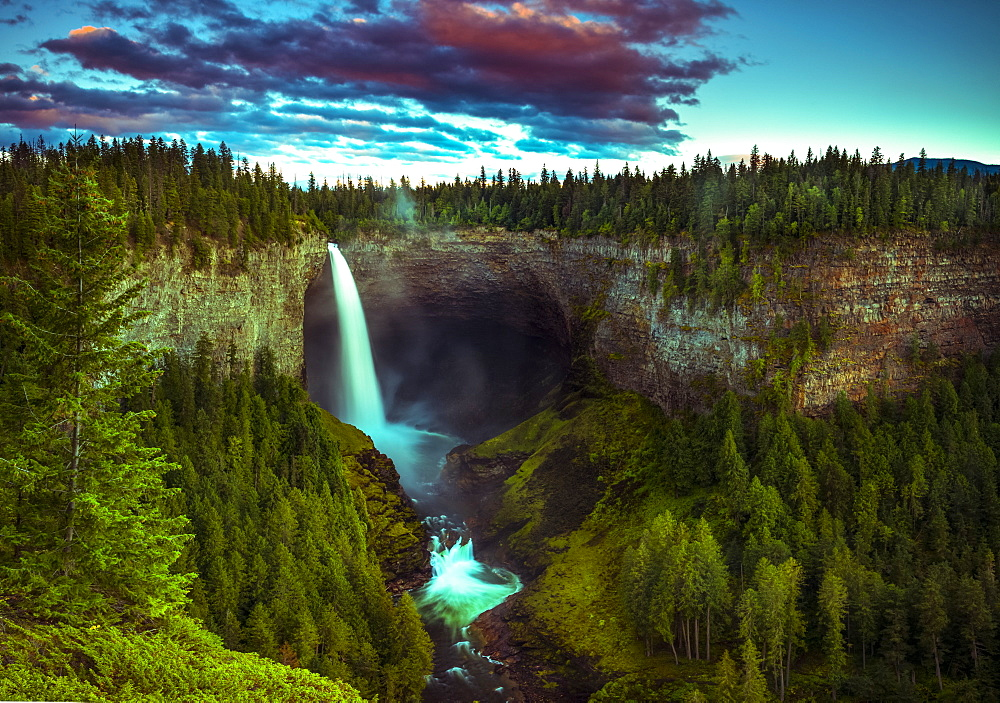 Illuminated waterfall flowing over a cliff in Wells Grey Provincial Park, Thompson-Nicola Regional District, British Columbia, Canada